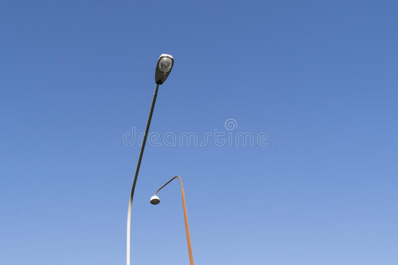 Lampposts against blue sky. Two high streetlights bending against a blue sky royalty free stock photo