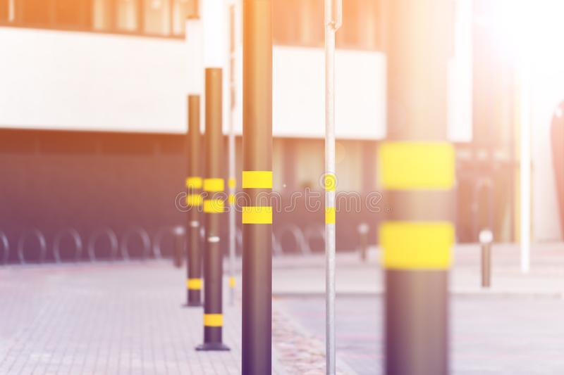 Lampposts of dark color. Lamp posts dark color. On poles inflicted stripes yellow. Metal posts. The background is blurred royalty free stock photos