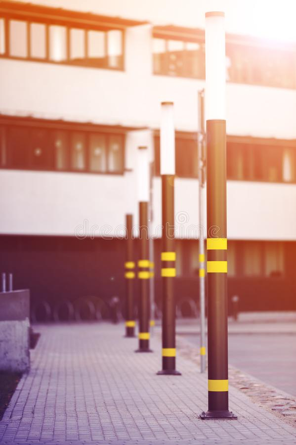 Lampposts of dark color. Lamp posts dark color. On poles inflicted stripes yellow. Metal posts. The background is blurred stock photos