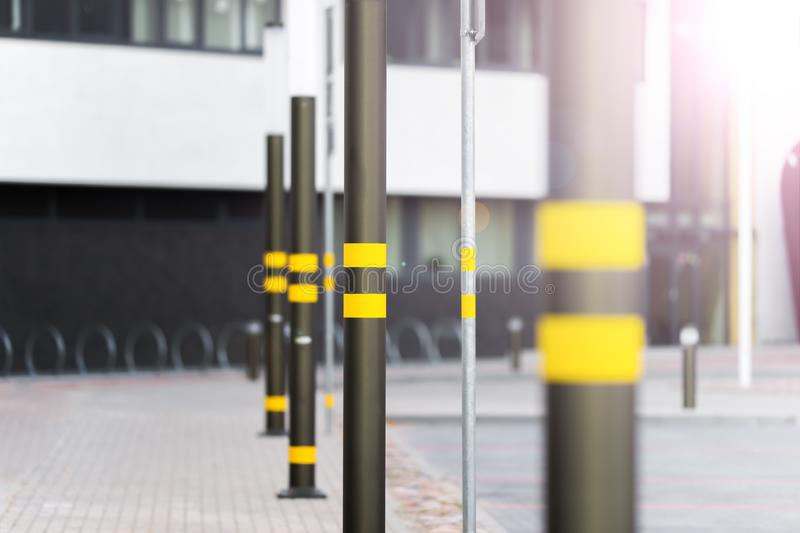 Lampposts of dark color. Lamp posts dark color. On poles inflicted stripes yellow. Metal posts. The background is blurred royalty free stock photo