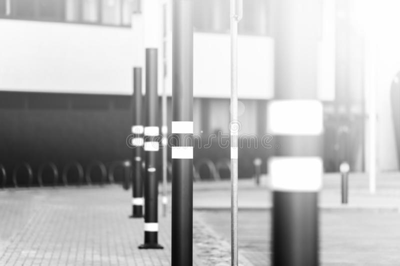 Lampposts of dark color. Lamp posts dark color. On poles inflicted stripes yellow. Metal posts. The background is blurred stock images