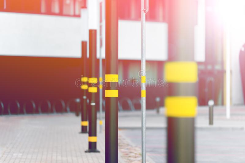 Lampposts of dark color. Lamp posts dark color. On poles inflicted stripes yellow. Metal posts. The background is blurred royalty free stock photography