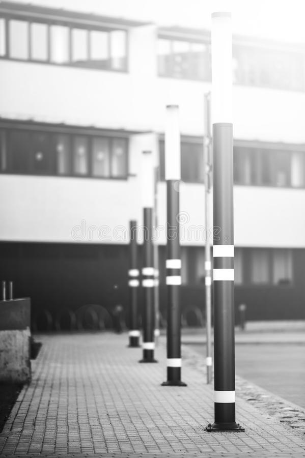 Lampposts of dark color. Lamp posts dark color. On poles inflicted stripes yellow. Metal posts. The background is blurred royalty free stock images