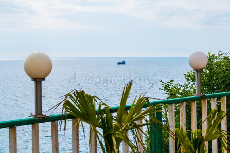Railing of terrace with sea view. Lampposts on railing and leaves of palm closeup on the background of sea with the fishing ship royalty free stock photo