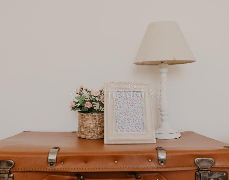 Lampram och blomma på en gammal resväska fotografering för bildbyråer