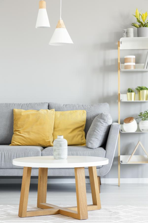 Lamps above wooden table in front of grey sofa with yellow pillo royalty free stock photo