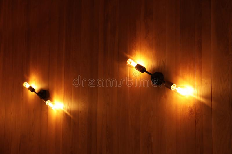 Lamps with glowing light bulbs on wooden wall. Indoors royalty free stock images