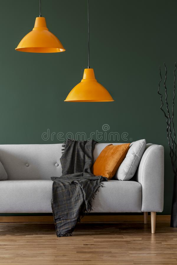 Lamps on a green wall and sofa in a simple living room interior. Orange lamps on a green wall and sofa in a simple living room interior stock photography