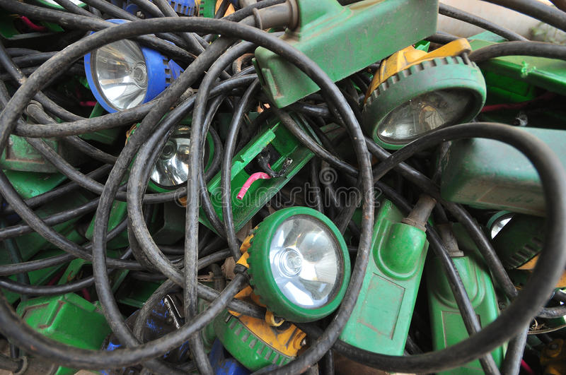 Lamps. A jumbled pile of underground mining lamps with battery packs. Disorganized with cables twisting in between the battery packs and lights royalty free stock image