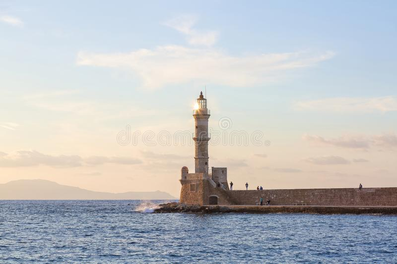 The lamps light up the lighthouse at the evening time. Ancient architecture. The location of the seaport Chania, Creete island. The lamps light up the stock photos