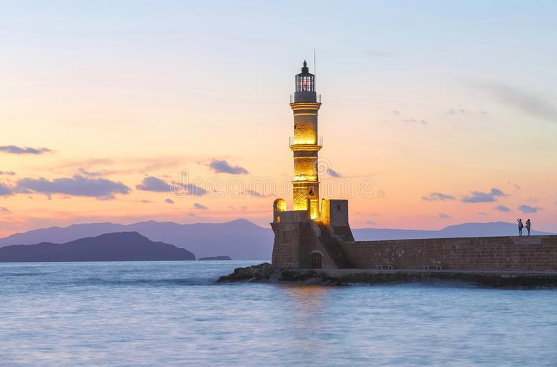 The lamps light up the lighthouse at the evening time. Ancient architecture. Seaport Chania, Creete island, Greece. Sunset. The lamps light up the lighthouse at royalty free stock images