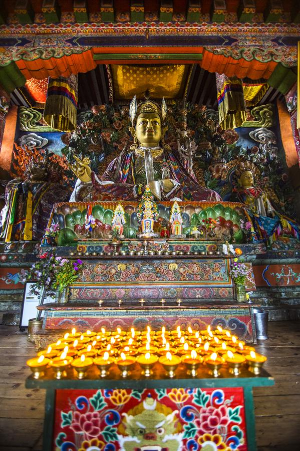 Lamps with statue of Guru Rinpoche and deity , inside of chapel , Bhutan. Many of offering lamps in front of statues of deity . the main statue is Guru Rinpoche stock image