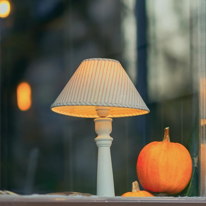 Lampshade and bright natural pumpkin in window, home decor for Thanksgiving day celebration. Luminous lampshade and bright natural pumpkin in window, home decor royalty free stock images