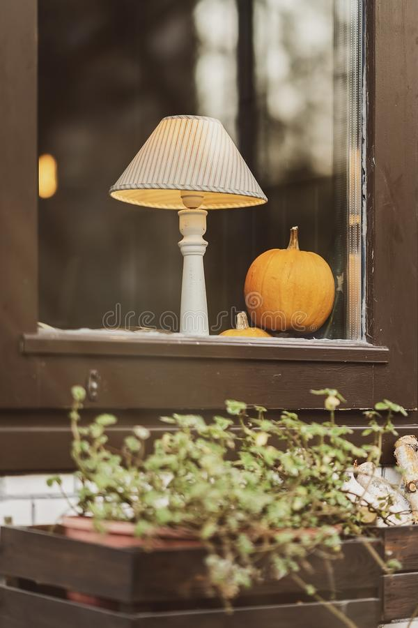 Lampshade and pumpkin on the windowsill, home decor for Thanksgiving day celebration. Autumn mood concept stock photos