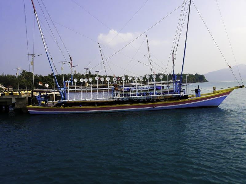 LAMPUNG, INDONESIË, 17 JULI 2019: Traditionele varende houten boot op het waterparkeren bij de haven in de zomervakantie binnen royalty-vrije stock foto