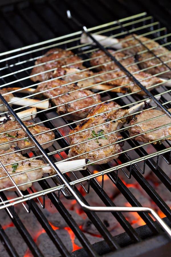 Lamskoteletten in het roosteren van mand bij de grill stock fotografie