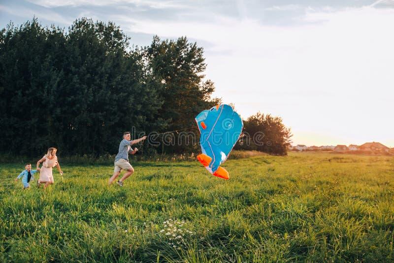 Lançamento feliz do filho do pai, da mãe e da criança da família um papagaio na natureza no por do sol foto de stock