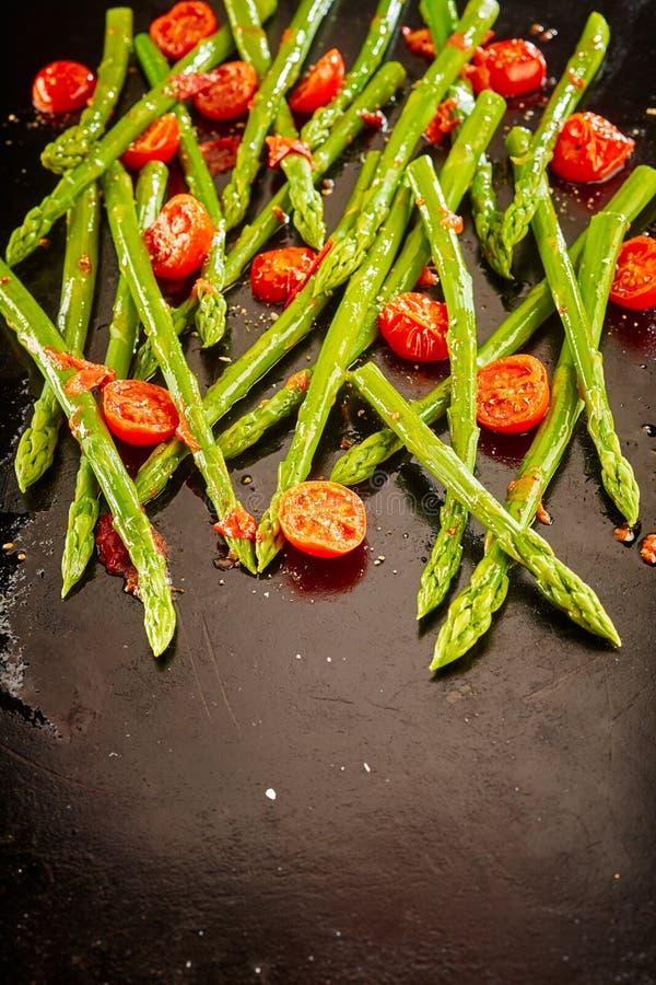 Lanças verdes frescas do aspargo com tomates roasted fotografia de stock royalty free