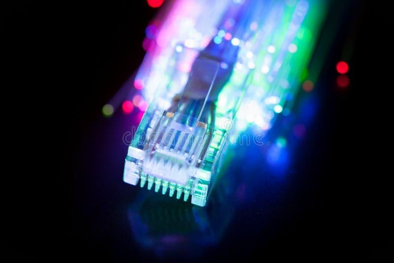LAN et câble de fibre optique sur le fond noir photographie stock