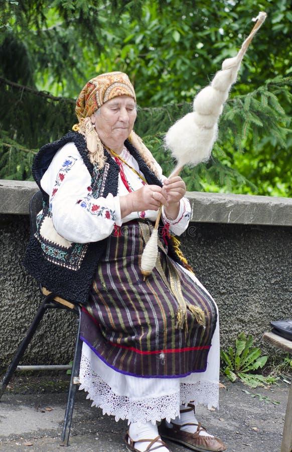 Lana di filatura della donna anziana fotografia stock