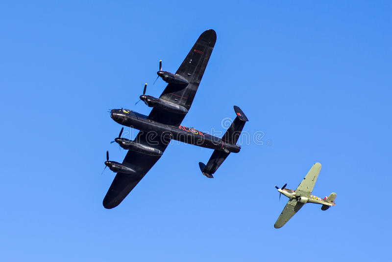 Lancaster Bomber and Hawker Hurricane. DARTMOUTH, UNITED KINGDOM - AUGUST 31: Lancaster Bomber PA474 and Hawker Hurricane Fighter Escort flying at the Dartmouth stock images