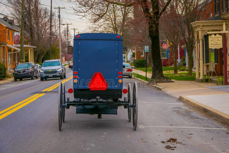 LANCASTER, USA - APRIL, 18, 2018: Outdoor view of the back of old fashioned Amish buggy with a horse riding on urban royalty free stock images