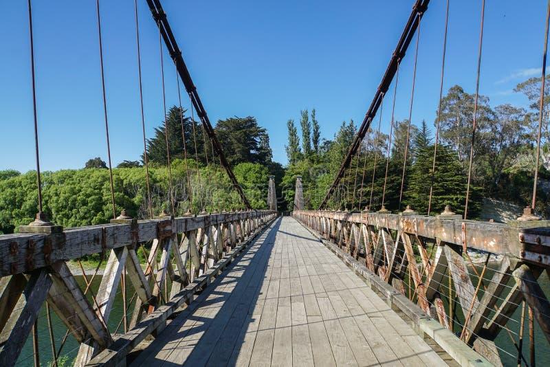Lance el puente con una honda de madera a través del río en Nueva Zelanda fotografía de archivo