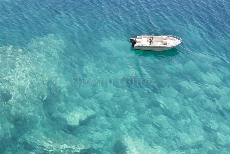 Lancha de carreras anclada en agua baja de la turquesa fotografía de archivo libre de regalías