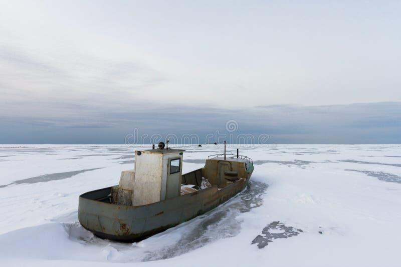 Lancha oxidada congelada en el lago ladoga foto de archivo