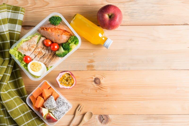 Lancheiras saudáveis no pacote plástico, no peito de frango grelhado com batata doce, no ovo e na salada vegetal, fruto, suco de  imagem de stock royalty free