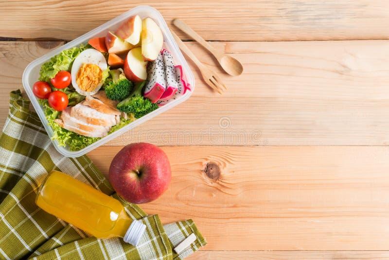 Lancheiras saudáveis no pacote plástico, no peito de frango grelhado com salada vegetal, no ovo e no fruto, suco de laranja Faça  foto de stock
