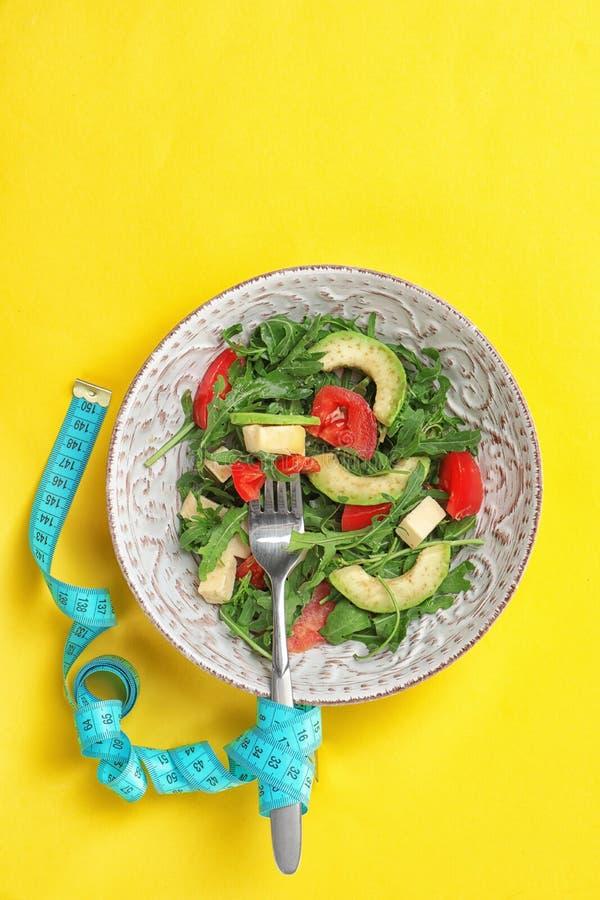 Lanci con l'insalata della verdura fresca e nastro adesivo di misurazione immagine stock