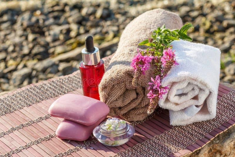 Lanci con sale marino, bottiglie con olio aromatico, il sapone, fiore selvaggio immagine stock libera da diritti