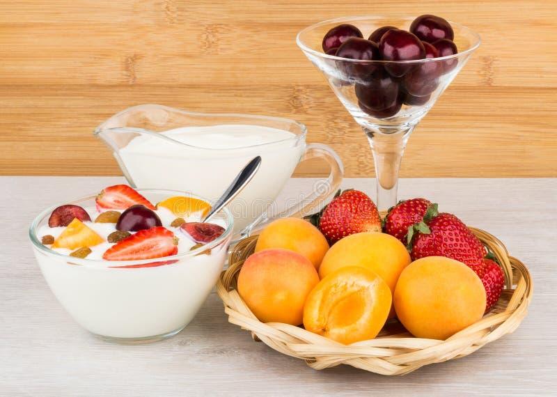 Lanci con yogurt, i pezzi dell'albicocca, le ciliege e le fragole immagine stock libera da diritti