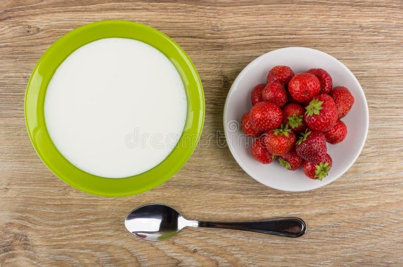 Lanci con yogurt, il piatto con le fragole ed il cucchiaio sulla tavola fotografie stock