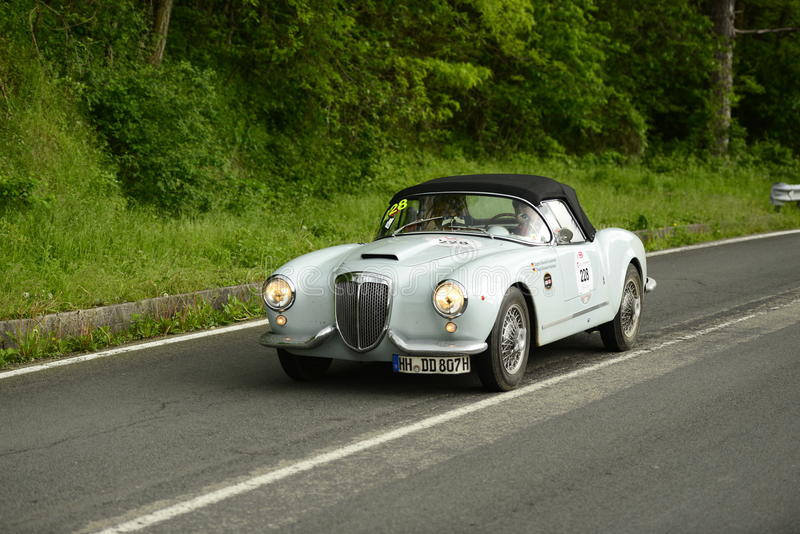 Lancia car running in Mille Miglia race. An old Lancia Aurelia B24 Spider (1952) runs in Mille Miglia 2013 race on May 18 in Loiano, Italy royalty free stock photos