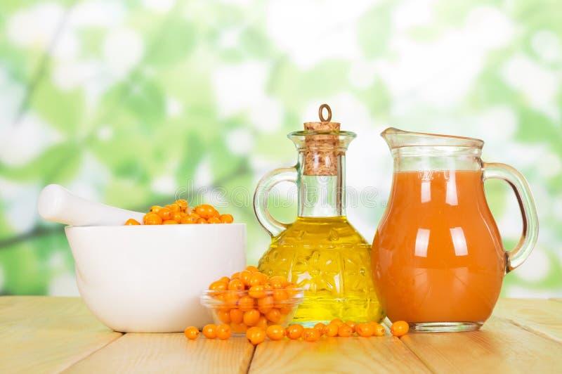 Lancia la bottiglia dell'olio dell'olivello spinoso, succo della brocca su verde astratto fotografia stock libera da diritti