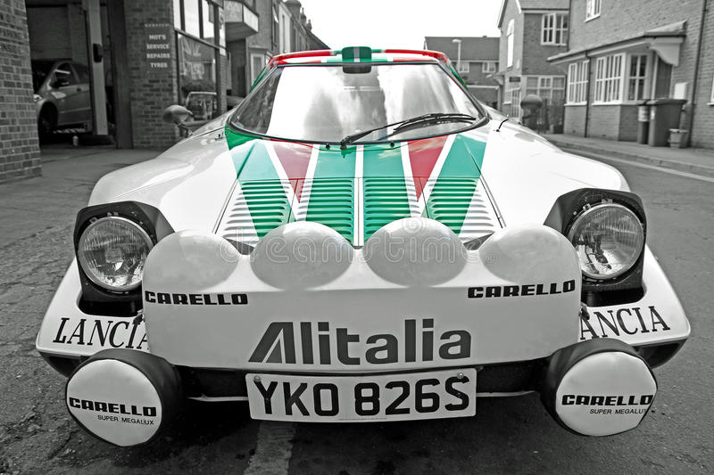 Lancia sponsored racing car. Photo of a lancia racing rally car with sponsorship red and green livery. photo ideal for showing sponsored racing team, racing cars royalty free stock images