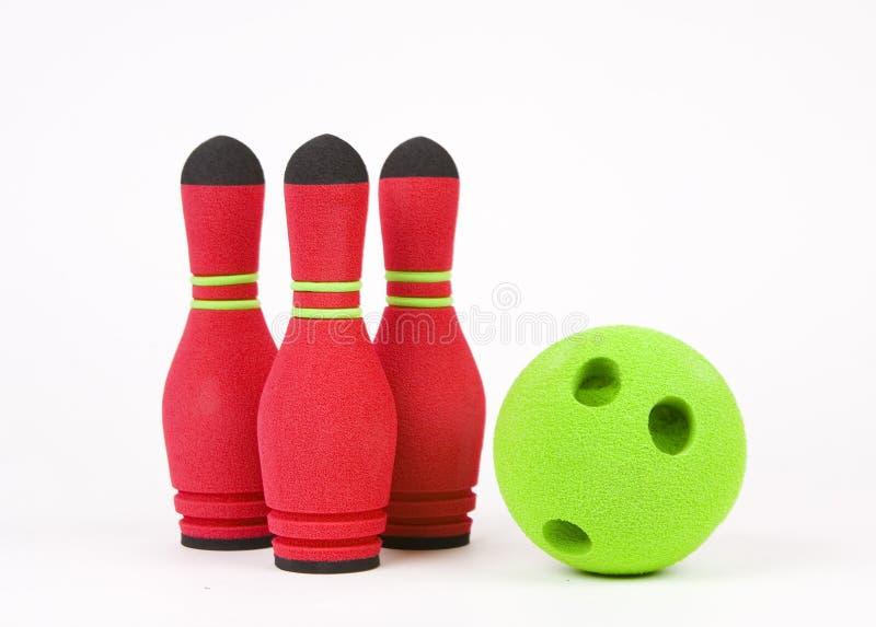Tre lanciare degli skittles e palla verde isolati su un fondo bianco fotografia stock