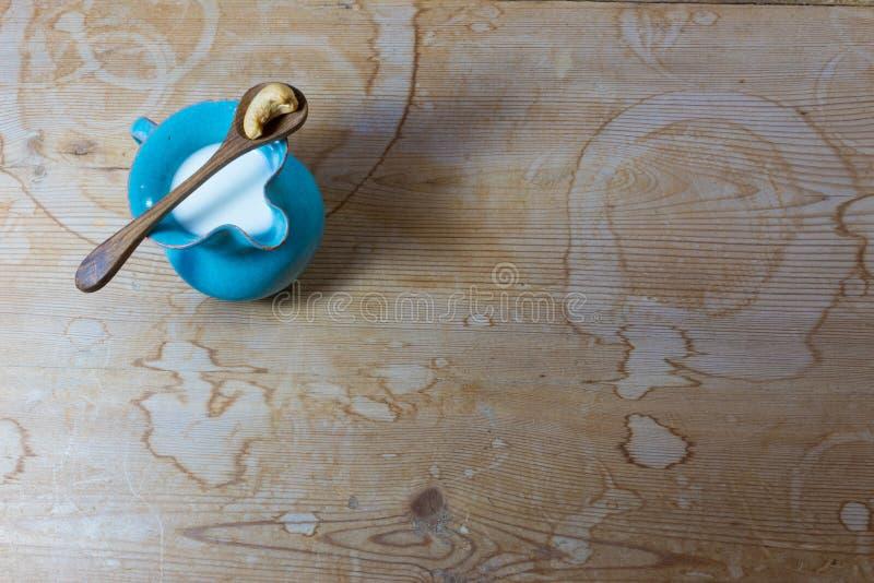 Lanciatore ceramico blu molto piccolo del latte dell'anacardio, cucchiaio di legno con il singolo anacardio, fondo di legno fotografia stock