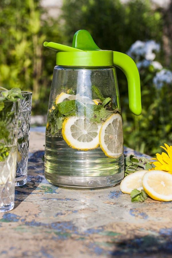 Lanciatore della limonata con il limone e la menta sulla tavola del giardino fotografia stock