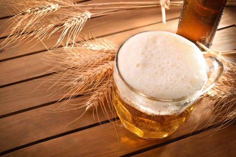 Lanciatore in pieno di birra con schiuma sulla vista superiore di legno immagini stock