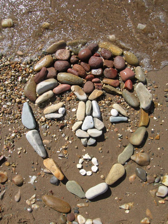 Land Art - african mask. Drawed with pebbles on the beach royalty free stock photography