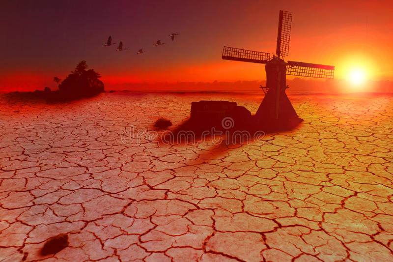 Land dryed by lack of water. Geese flying on a sunny dry land and over the windmill land due to the global warming, concept stock images