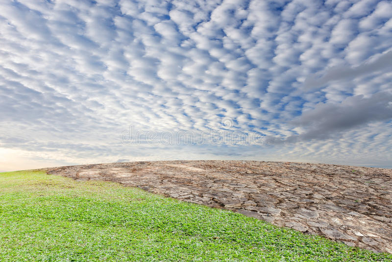 Land en gebarsten aarde met groene gras dramatische hemel, mede ecologie royalty-vrije stock foto