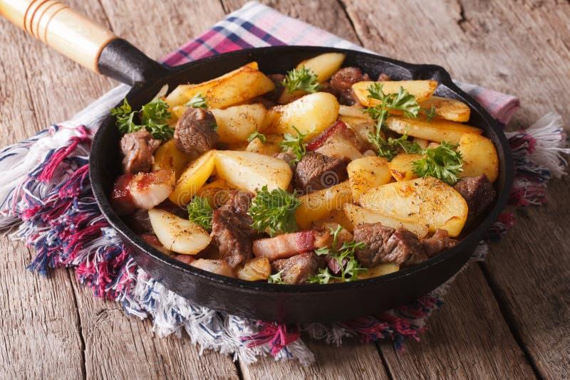 Land gebraden aardappels met vlees en bacon in een panclose-up Hor royalty-vrije stock foto
