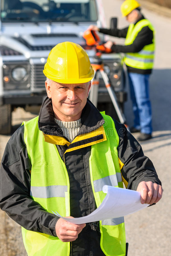 Land geodesist man hold plan reflective vest stock images