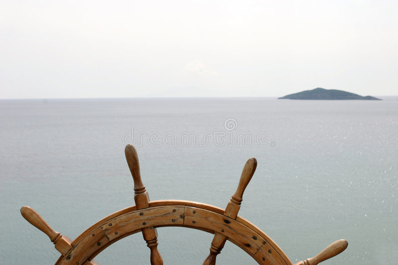 Land ho!. Old ship's steering wheel on great ocean background with a small island ahead royalty free stock photography