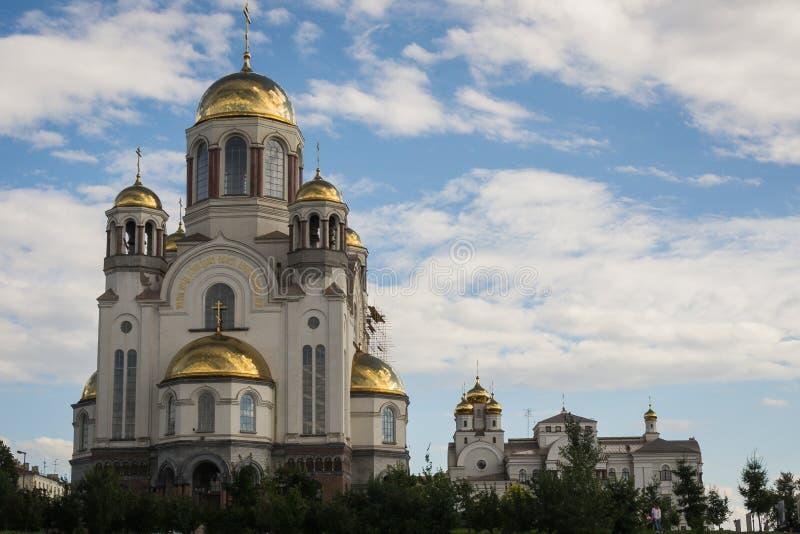 Land-Kirche mit Friedhof und hoher Helm am Sommer-Tag gegen blaue Wolke verzierten Himmel stockfotos