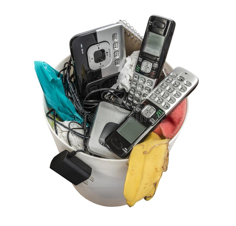 Land Line Telephones Thrown Away. Horizontal shot of land line telephones thrown away in a trashcan.  This shot is looking down on the trashcan royalty free stock photography
